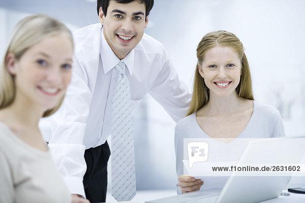 Büroangestellte lächeln vor der Kamera  eine Frau hält ein Dokument in der Hand