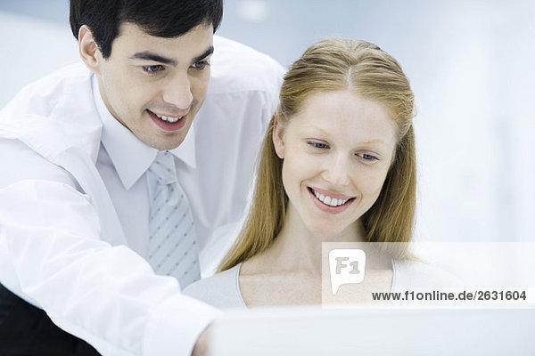 Professioneller Mann  der über die Schulter der Kollegin schaut und auf den Laptop zeigt.