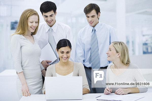 Gruppe von Fachleuten versammelt um Laptop-Computer  lächelnd
