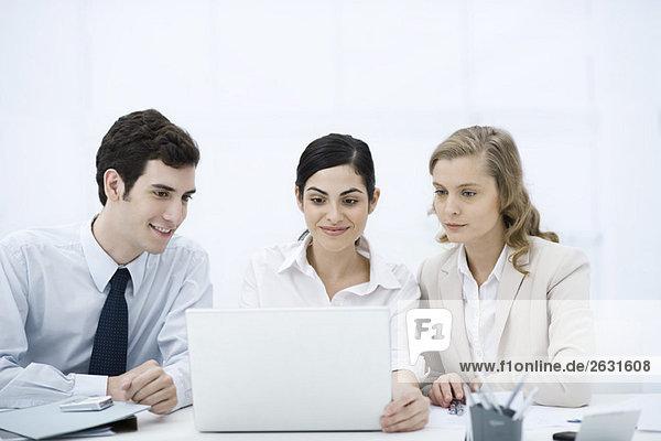 Drei Profis  die gemeinsam auf den Laptop schauen  lächelnd