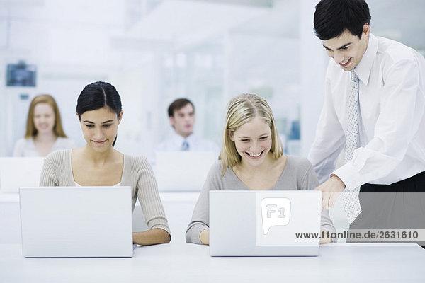 Büroarbeiterin mit Laptop  männlicher Vorgesetzter schaut über die Schulter und zeigt