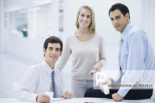 Drei Profis bei einer Kaffeepause  lächelnd vor der Kamera