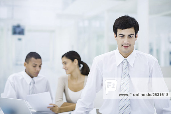 Geschäftsmann im Büro  lächelt in die Kamera  Mitarbeiter im Hintergrund