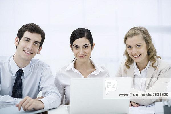 Team von Profis sitzt mit Laptop-Computer  lächelnd vor der Kamera