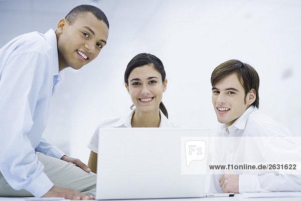 Junge Profis versammelten sich um Laptop-Computer  lächelnd vor der Kamera