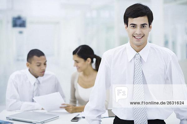Geschäftsmann lächelt in die Kamera  Kollegen arbeiten im Hintergrund