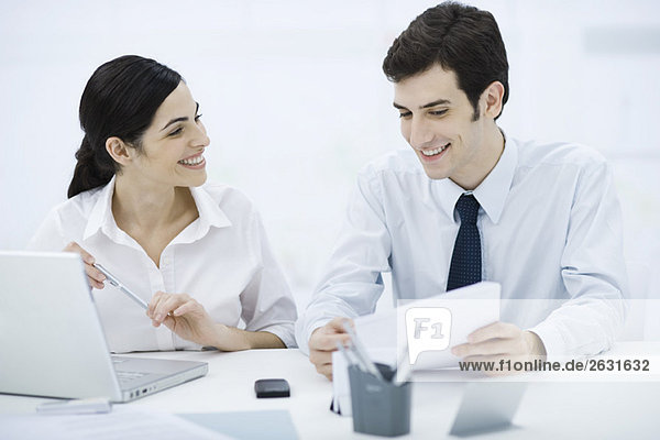 Profis arbeiten zusammen am Schreibtisch  Mann hält Dokument