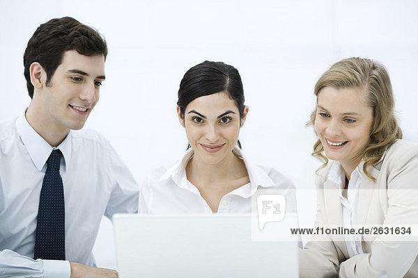 Drei Profis versammelten sich um Laptop-Computer  Frau in der Mitte lächelnd in der Kamera