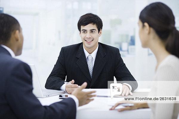Geschäftsmann sitzt am Schreibtisch  spricht mit Kunden und lächelt