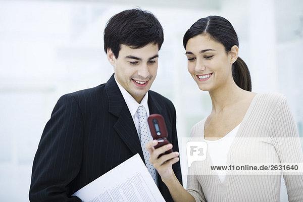 Kollegen schauen gemeinsam auf das Handy  lächelnd