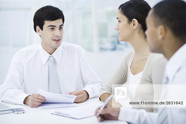 Profis am Tisch sitzen und Dokumente diskutieren