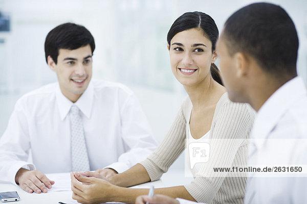 Junge Profis sitzen am Tisch  Fokus auf die Frau im Zentrum