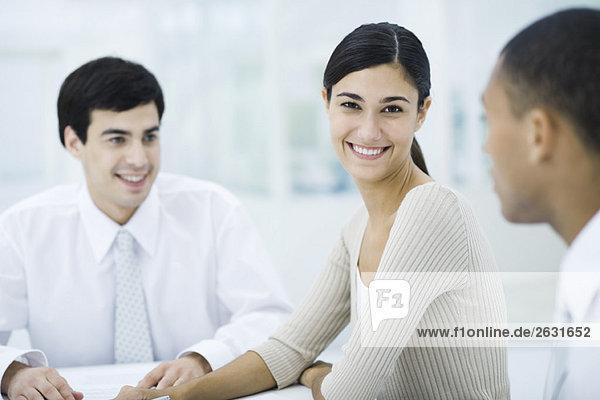 Junge berufstätige Frau sitzt mit männlichen Kollegen  lächelnd vor der Kamera