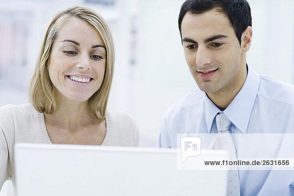 Zwei Profis  die gemeinsam auf den Laptop schauen  lächelnd