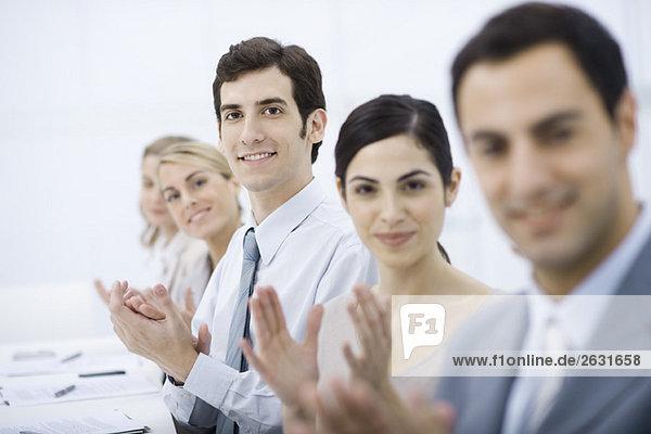 Gruppe von Profis klatschend  lächelnd vor der Kamera