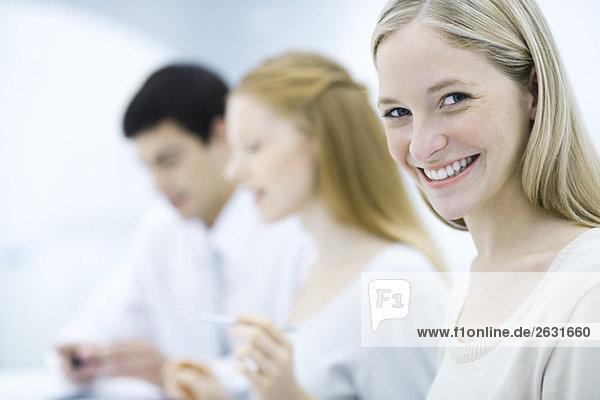 Junge Berufsfrau lächelt vor der Kamera  Kollegen arbeiten im Hintergrund