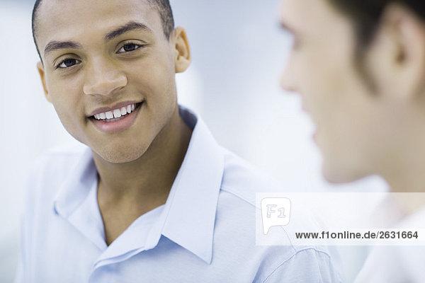 Junger Profi lächelnd vor der Kamera  Kollege im Vordergrund