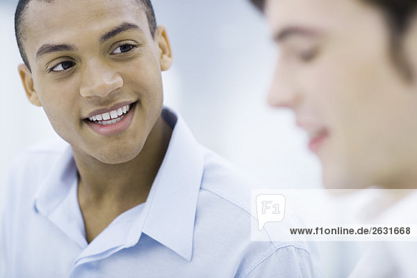 Junger professioneller Mann im Gespräch mit Kollegen  lächelnd