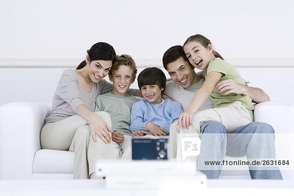 Familie sitzt zusammen auf Sofa  posiert für Digitalkamera im Vordergrund