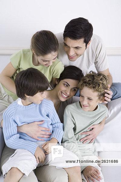 Familie auf dem Sofa sitzend  Söhne auf dem Schoß der Mutter sitzend  Hochwinkelansicht
