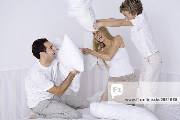 Eltern und kleiner Sohn mit Kissenschlacht auf dem Bett