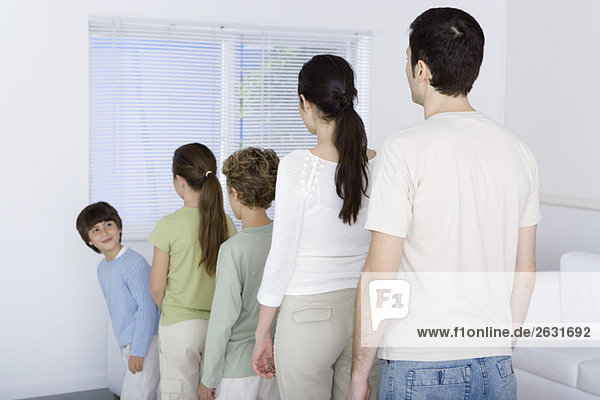 Family lined up shortest to tallest  youngest boy looking over shoulder at rest of family