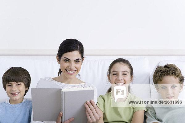Mutter sitzt mit drei Kindern auf dem Sofa  liest Geschichte  alle lächelnd vor der Kamera.