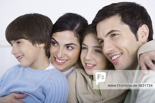Eltern und zwei Kinder umarmend  Wange an Wange  Nahaufnahme