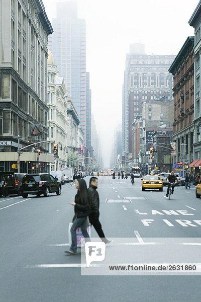 Fußgänger überqueren die Straße in der W 19th Street und 6th Avenue Chelsea  New York  mit Blick auf NE