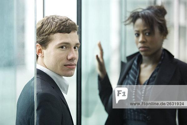 Geschäftsmann und Geschäftsfrau schauen mit Unsicherheit in die Kamera