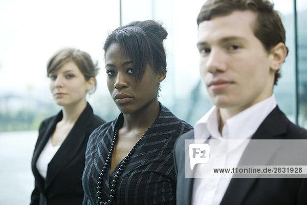 Drei Geschäftspartner stehen nebeneinander und schauen in die Kamera.