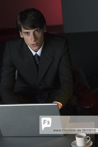 Geschäftsmann mit Laptop im dunkel beleuchteten Café  Blick auf Kamera