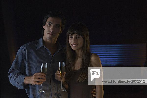 Paar hält Gläser Champagner  lächelt in die Kamera  Portrait