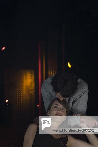 Paar  Frau sitzend  Mann hinten stehend  nach vorne lehnend  sie auf die Stirn küssend