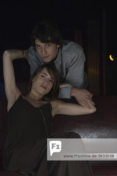 Paar lächelt in die Kamera  Frau sitzt mit erhobenen Armen und umarmt den Mann  der dahinter steht.