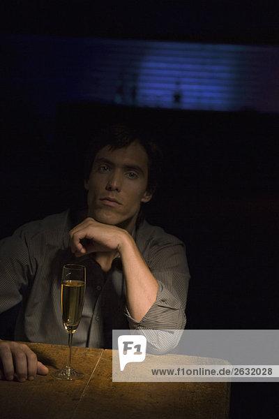 Mann sitzt im Dunkeln  Hand unter dem Kinn  Scheinwerfer auf Glas Champagner auf Tisch