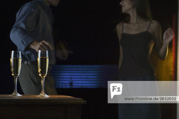 Champagnergläser  Pärchen tanzen im dunkel beleuchteten Hintergrund