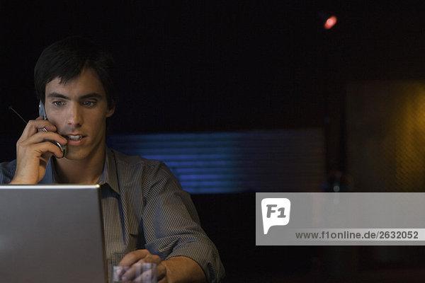 Mann spricht auf dem Handy  mit Laptop-Computer