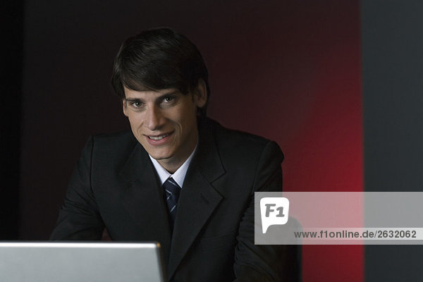 Geschäftsmann lächelt Kamera über Laptop  Portrait