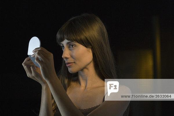 Frau schaut sich selbst im Handspiegel an