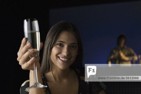 Frau hält ein Glas Champagner hoch  lächelt in die Kamera  Barkeeper im Hintergrund