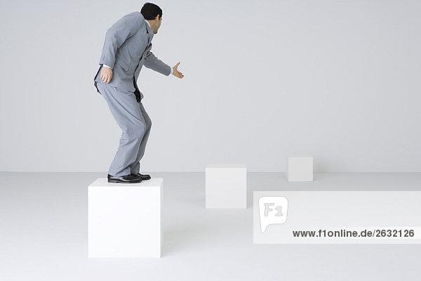Geschäftsmann auf Block stehend  Hand ausstreckend Geschäftsmann auf Block stehend, Hand ausstreckend