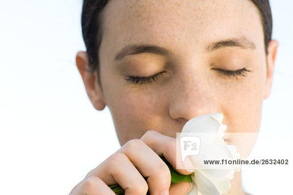 Young Woman smelling weiß stieg Blüte  Augen geschlossen  Nahaufnahme Young Woman smelling weiß stieg Blüte, Augen geschlossen, Nahaufnahme