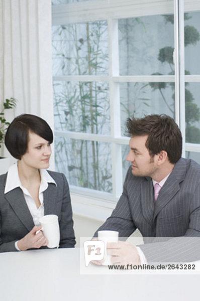 zwei Geschäftsleute sitzen am Tisch mit Pause