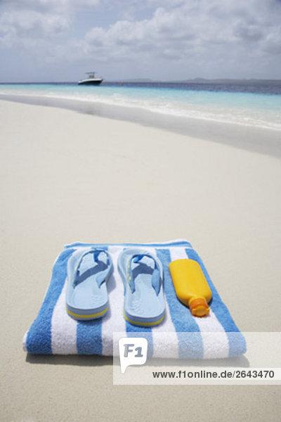 paar Flip flops Handtuch und Sun Lotion auf Sandstrand