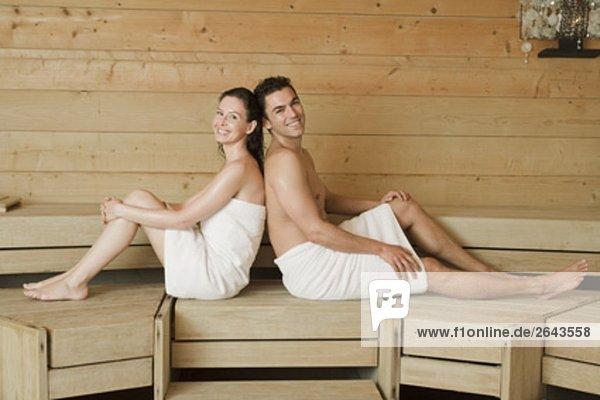Frau und Mann entspannende Sauna Sitzung wieder