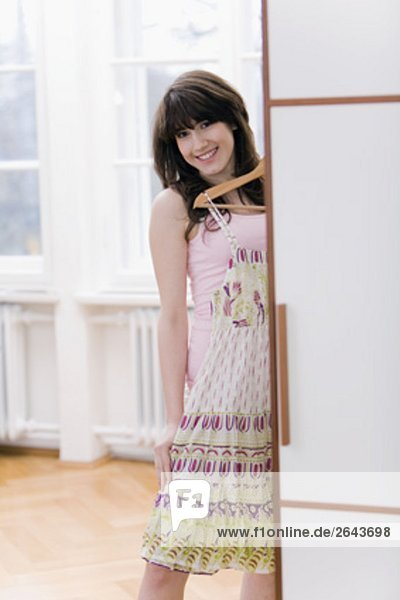 teenage girl in front of wardrobe trying on new dress