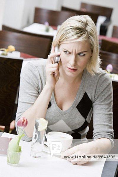 junge Frau sitzen am Restaurant Tisch auf Handy
