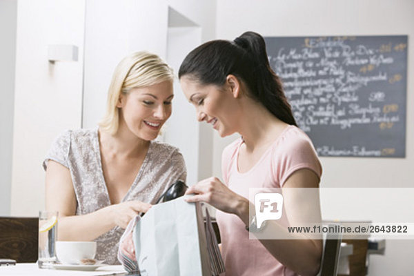 two female friends at restaurant looking at content of shopping bag