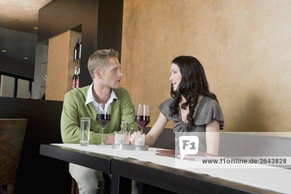 junges paar Restaurant mit Gläsern Rotwein sitzend